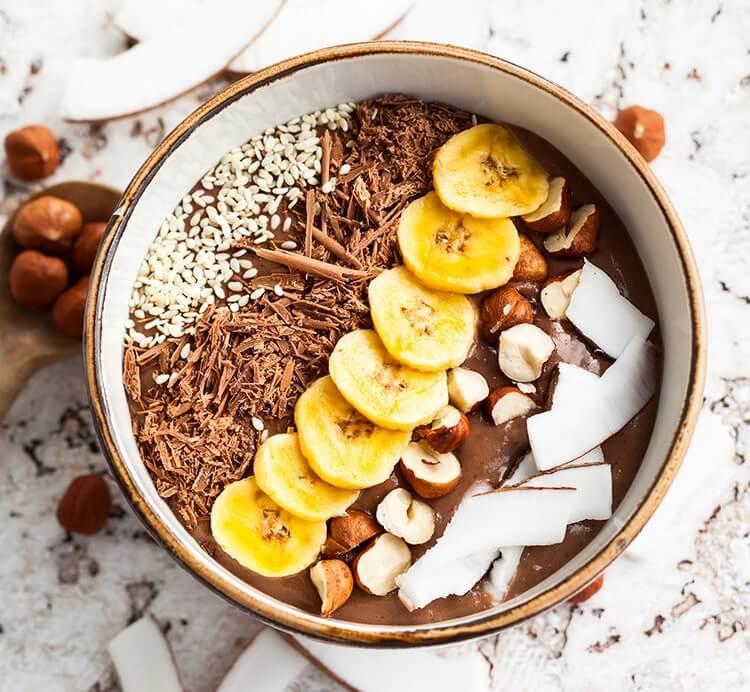 Smoothie mit Kokoschips, Banane und Haselnusskernen